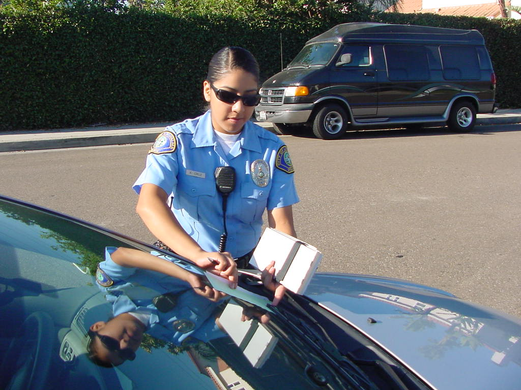 Police Officer Putting Ticket Under Windshield Wiper on Car